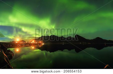 Northern lights over fjord. Night landscape of northern lights.
