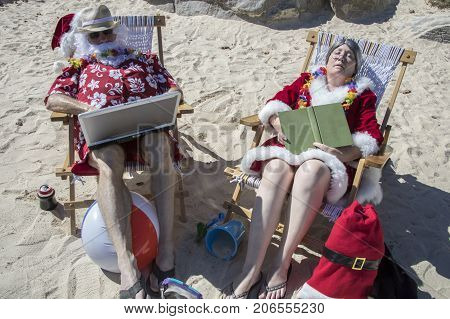 Santa And Mrs Claus Reading And Working On Beach