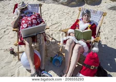 Santa Claus Working On Laptop Computer And Mrs Claus Reading On Sandy Beach