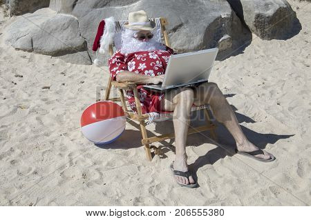 Santa Claus Working On Beach With Laptop Computer On Vacation