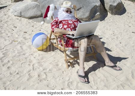 Santa Claus Working On Beach Chair Working With Laptop Computer On Vacation