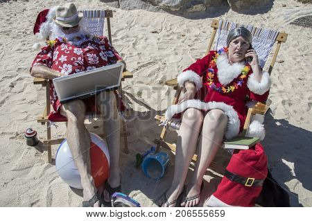 Santa Claus On Laptop Computer And Mrs Claus On Phone On Sandy Beach