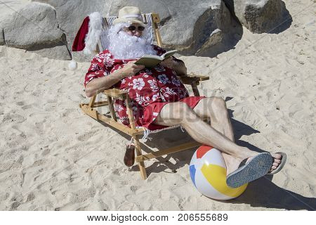 Santa Claus Reading Novel On Sunny Beach