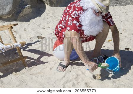 Santa Claus Digging In Sand With Pale And Shovel On Beach Ball