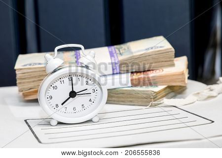 Money clock alarm clock and a folder with documents. Current payments on monetary obligations