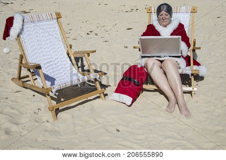 Mrs Claus working on laptop computer sitting in lounge chair on sandy beach.