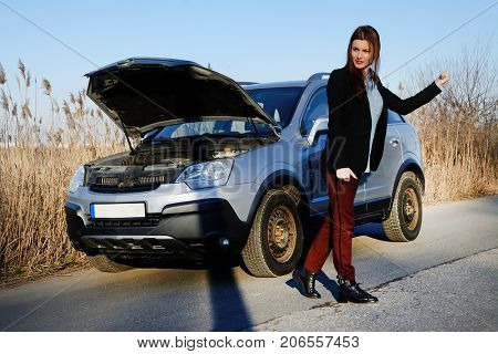 Young woman and broken down car on road, checking problems at the engine