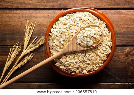 Oat Flakes, Uncooked Oats In Bowl With Wooden Spoon And Wheat Ears