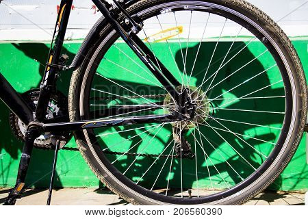 Rear bicycle wheels near the white wall