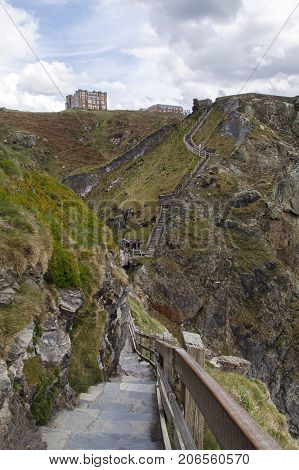 Cornwall, UK: April 14, 2016: The cliff path leading to Tintagel Castle. Hotel Camelot is high on the cliff with views over the bay.