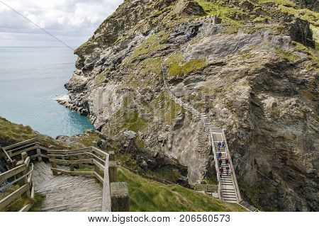 Cornwall, UK: April 14, 2016: The dramatic cliff path leading to Tintagel Castle. The castle is controlled and maintained by English Heritage and is a popular tourist destination all year round