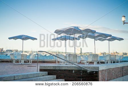 View of patio with umbrella chairs and tables behind moakley courthouse on waterfront in boston seaport harbor