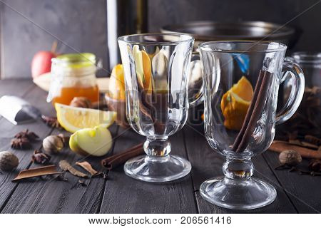 Mulled wine recipe ingredients , christmas or winter warming drink. Bottle of wine, honey, orange, cinnamon sticks, anise, nutmeg, cloves and glass from above.