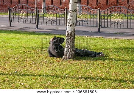 A drunkard lying on the grass wakes up on a sunny afternoon