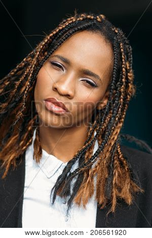 Confident young African American female. Pretty black woman in selective focus, contemptuous expression, girl on dark background, disdain concept