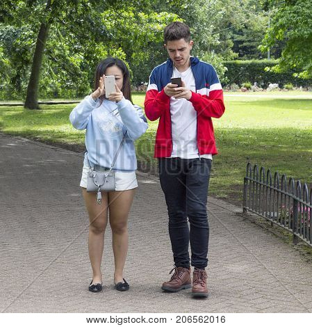 Cardiff, UK: August 05, 2016: Two young adults playing Pokemon Go the free-to-play location based augmented reality mobile game. They are looking at their smart phones while and facing the camera.