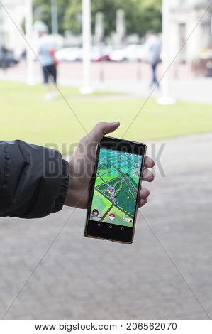 Cardiff, UK: August, 2016: Man holding a cellphone while playing Pokemon Go and try to catch a monster. Pokémon Go is a free-to-play location based augmented reality mobile game developed by Niantic.