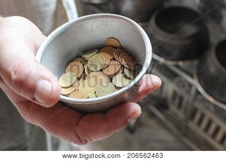 Holding a begging bowl out to recieve money in Thailand