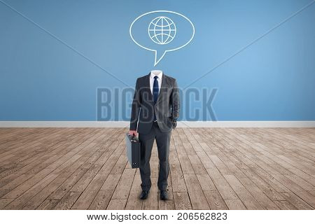 Headless businessman standing with briefcase against room with wooden floor