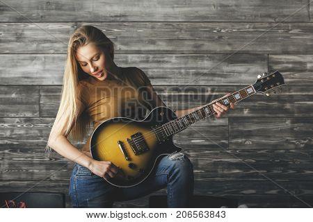 Seductive Woman Playing The Guitar