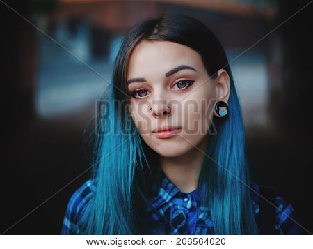 Street punk or hipster girl with blue dyed hair. Woman with piercing in nose, violet lenses, ears tunnels and unusual hairstyle stands in city.
