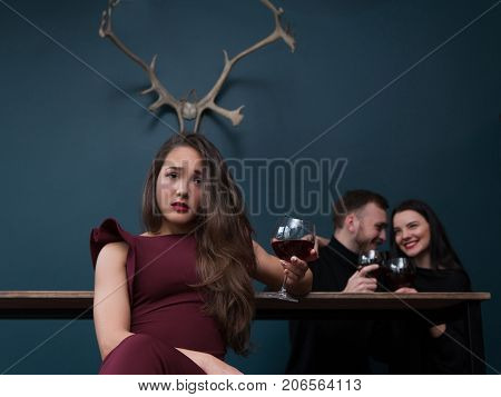 Cheating relationships. Sad betrayed girl. Love affair behind back, male cheater with friend. Unfaithful partner, pretty female with horns on blue background in focus on foreground