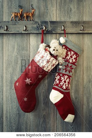 Pair of Christmas stockings hanging from hooks with reindeer figures sitting on the ledge