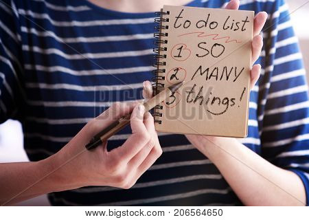 Close up of woman hands writing to do list in spiral notepad