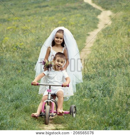 Young bride and groom playing wedding summer outdoor. Children like newlyweds on bicycle. Bridal, wedding concept, image toned and noise added.