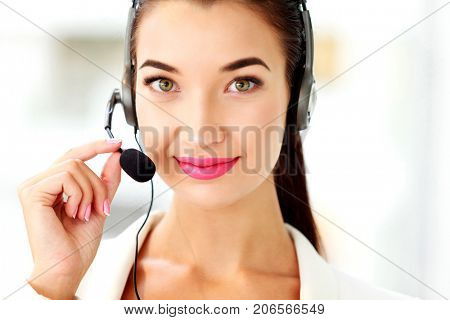 Closeup portrait of support phone operator in headset at workplace
