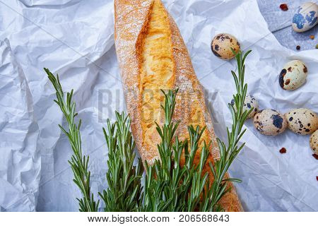 Close-up of a gray table with white wheat baguette, little-speckled quail eggs, twigs of aromatic rosemary, a white crumpled sheet of paper on a light gray background, top view.