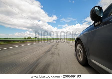 The car moves at high speed at the sunny day.