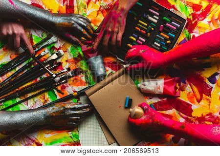Hands paint art in art studio colorful creative background. Red and silver hands paint picture on kraft paper. Modern art and art therapy drawing lessons at school. Pastel pencils and watercolors