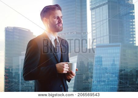 Side view of handsome smiling young businessman drinking coffee on abstract city background with sunlight. Success concept. Double exposure