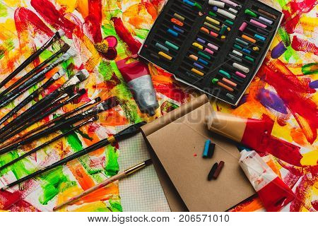 Brush palette tools for creative work on abstract artistic background closeup. Vintage stylized multicolor artists brushes and oil paint tubes artist paintbrushes paper. Top view art paint tubes