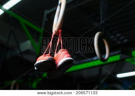 Pink bright sneakers for women hanging on crimson shoelaces on rings, steady rings or still rings, equipment for sports routine on a dark blurred background.
