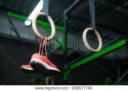 Pink vivid sneakers hanging on wooden steady rings on crimson shoelaces, sports routine, equipment for sports competitions on a dark blurred background.