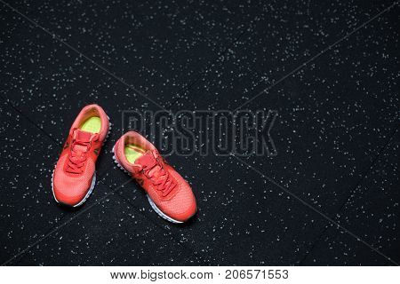 Top view of vivid pink sneakers, shoes for sports competitions, jogging, routines, workouts, long-distance running on a dark blurred background, copy space.
