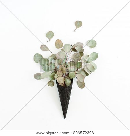 Black ice cream waffle cone with dry eucalyptus leaves isolated on white background. Flat lay top view flower concept.