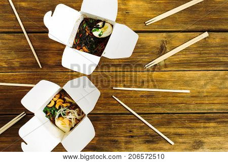 Noodles in box and chopsticks on wooden table background. Flat lay top view. Chinese takeaway food concept.