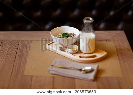 A close-up of beautiful lunch composition. A healthy salad with creamy sauce and a milkshake on a wooden table background. A set of organic dishes and a metal spoon. Copy space. Restaurant concept.