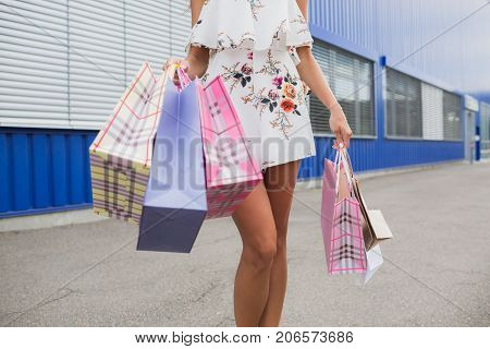 Body parts image, horizontal, lady's legs doing shopping. Sale in the city, consumerism and people concept - young woman with shopping bags walking in mall, bags by store. Buying clothes.