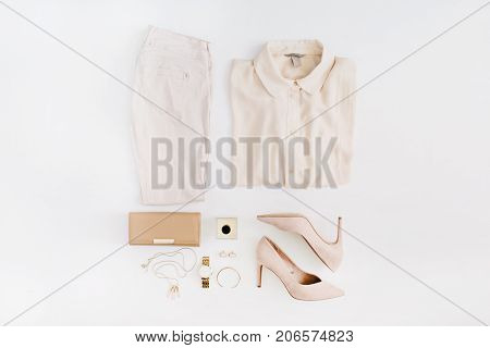 Women modern fashion clothes and accessories. Flat lay female casual style look with pastel pink jeans blouse high heels perfume gold watch. Top view.