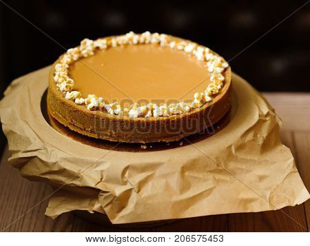 Close-up of a large round cake with condensed milk and a shortbread on a paper stand and on a black blurred background. Sweet and tasty dessert with popcorn on a top.