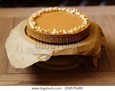 A view from above of a large round cake with condensed milk and a shortbread on a paper stand and on a blurred background. Sweet and tasty dessert with popcorn on a top, close-up.