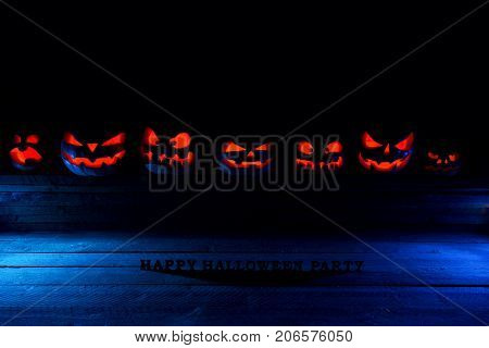 The Concept Of Halloween. Many Evil Scary Pumpkins In The Dark With A Blue Ice Glow. Jack Lantern Am