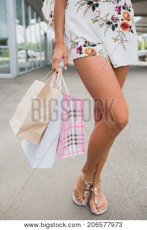 Body parts image, vertical, lady's legs doing shopping. Sale in the city, consumerism and people concept - young woman with shopping bags walking in mall, bags by store. Buying clothes.