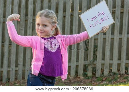 adorable school age girl wearing pink and holding sign that says i am the future for women's rights