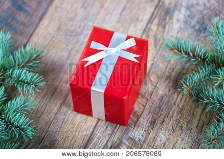 Close-up decorative red present box with a white ribbon and bowtie next to aromatic pine branch on a wooden rustic background.