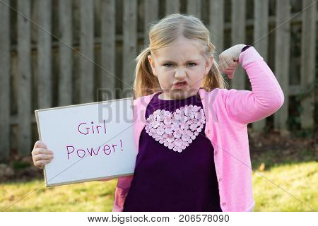 adorable school age girl wearing pink and holding sign that says girl power for women's rights
